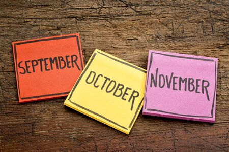 September, October and November - handwriting in black ink on sticky notes against rustic wood Stock Photo