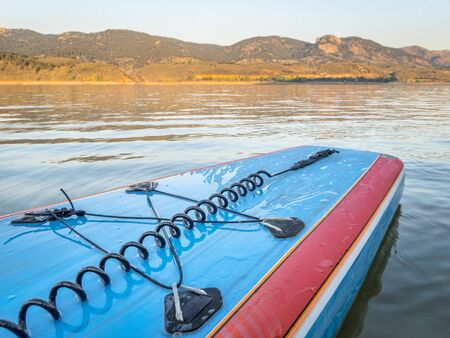 A tail of stand up paddleboard with a leash and bungees on a mountain lake (Horsetooth Reservoir), late summer morning Stock Photo