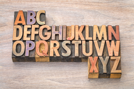 English alphabet abstract in vintage letterpress wood type printing blocks against grained wood Stock Photo