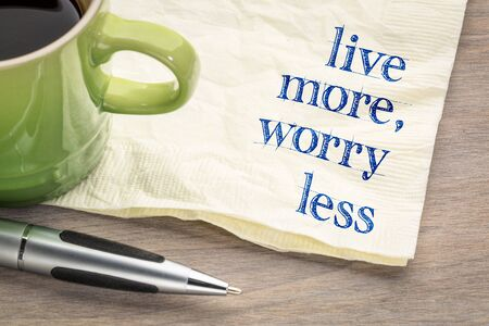 live more, worry less text - inspirational handwriting on a napkin with a cup of coffee Stock Photo