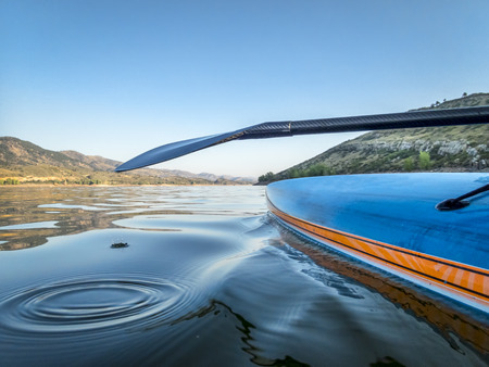 Stand up paddleboard with a carbon fiber paddle - low angle view on Horsetooth Reservoir in northern Colorado Stock Photo
