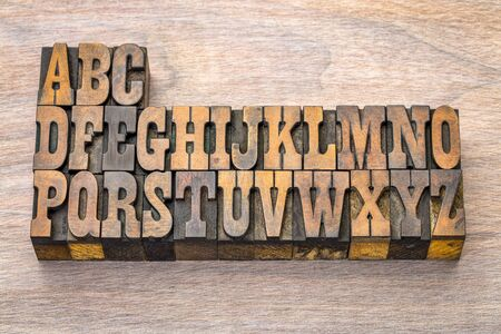 English alphabet abstract in vintage letterpress wood type printing blocks against grained wood, French Clarendon font popular in western movies and memorabilia