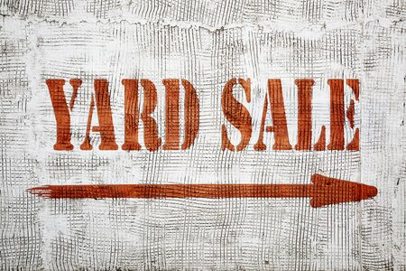 yard sale - graffiti sign with an arrow on stucco wall Stock Photo