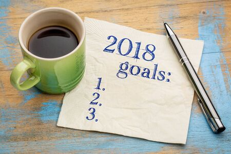 2018 year goals list on a napkin on a wood table with  a cup of coffee Stock Photo