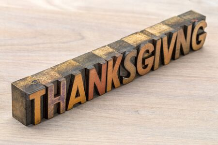 Thanksgiving word abstract in vintage letterpress wood type against grained wood