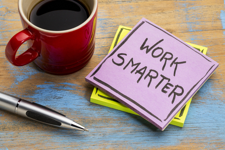 Work smarter  - handwriting in black ink on a sticky note with a cup of coffee Stock Photo