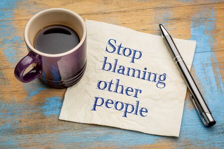 Stop blaming other people advice or reminder - handwriting on a napkin with a cup of espresso coffee Stock Photo