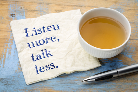 Listen more, talk less - motivational text on a napkin with a cup of tea