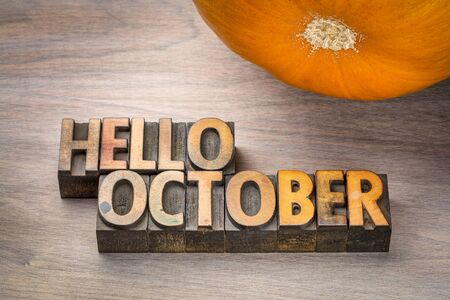 hello October greeting card - letterpress wood type blocks against grained wood with a pumpkin Stock Photo