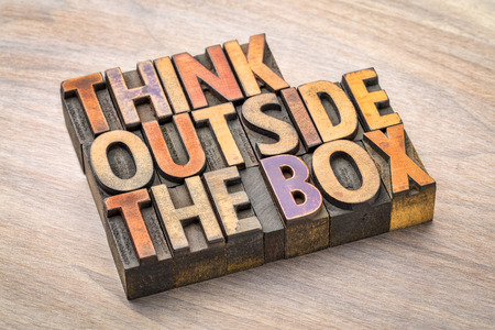 think outside the box concept- motivational phrase in vintage letterpress wood type against grained wood