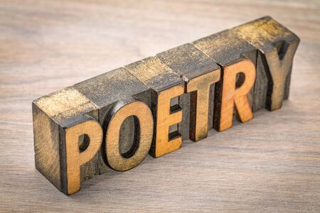 poetry word abstract- text in vintage  letterpress wood type printing blocks against grained wood Stock Photo