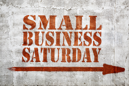 Small business Saturday  - graffiti sign with arrow on stucco wall Imagens