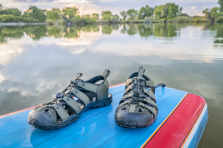 water sandals on a deck of stand up paddleboard, late summer lake scenery