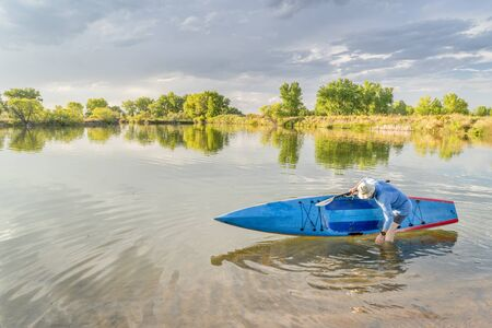 Male senior paddler rinsing his stand up paddleboard on a lake, late summer scenery in northern Colorado Stock Photo