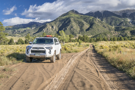 Great Sand Dunes National Park and Preserve - September 15, 2017: Toyota 4runner SUV (2016 Trail edition) with recovery sand ladders on roof driving on a sandy Medano Pass Road in late summer.