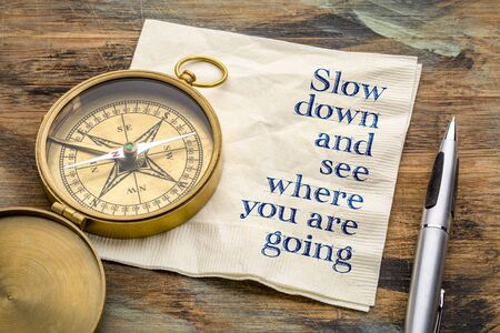 Slow down and see where you are going - inspiraitonal handwriting on a napkin with an antique brass compass