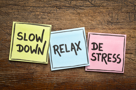 slow down, relax, de-stress concept -  motivational lifestyle reminders on colorful sticky notes against rustic wood