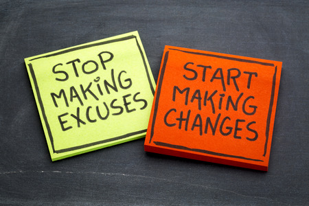 Stop making excuses, start making changes - handwriting on sticky notes against slate blackboard Stock Photo