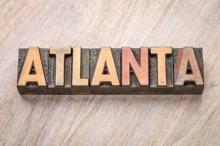 Atlanta word abstract in vintage  letterpress wood type against grained wooden background