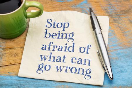 Stop met bang te zijn voor wat er mis kan gaan - handschrift op een servetje met een kopje koffie
