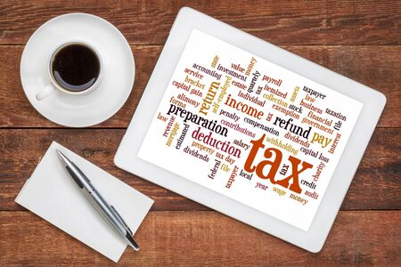 cloud  of words related to taxes, preparation, paying, income, refunds  on a digital tablet with a cup of coffee