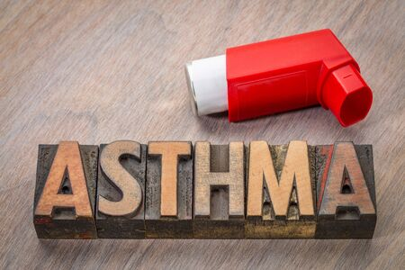 asthma word abstract in vintage letterpress wood type with an inhaler