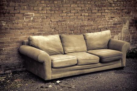 古いソファーに囲まれた路地で破棄ゴミやレンガの壁に、ガラスの破片でセピア調の画像