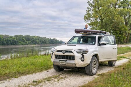 Dalton Bottom, MO, USA - August 14, 2017: Loading stand up paddleboard on a roof of Toyota 4Runner (2016 Trail Edition) SUV on a shore of the Missouri RIver. Editöryel