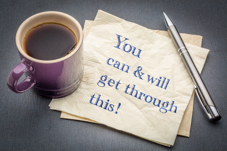 You can and will get through it - positive handwriting on a napkin with cup of coffee against gray slate stone background Stock Photo