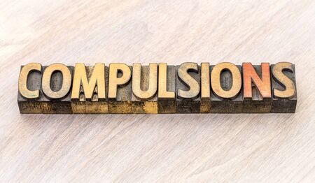 compulsions - word abstract in vintage letterpress wood type printing blocks Stock Photo
