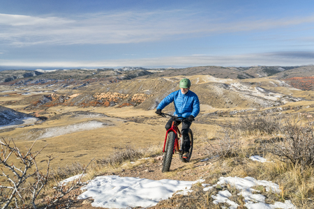 a senior male riding a fat bike on Cheyenne Rim in Red Mountain Open Space, late fall scenery with some snow