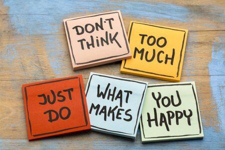Não pense muito, apenas faça o que te faz feliz - caligrafia em notas Foto de archivo - 89875586
