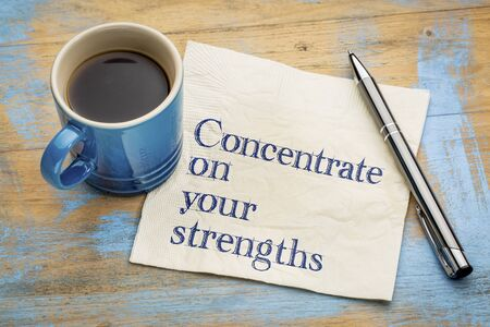 Concentrate on your strengths - handwriting on a napkin with a cup of espresso coffee Stockfoto