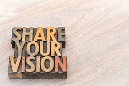Share your vision word abstract in vintage letterpress wood type against grained wood with a copy space
