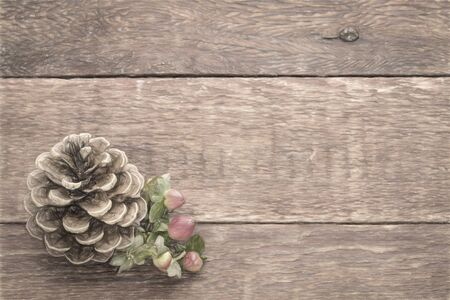 Pine cone with red berries against rustic barn wood with a copy space, digital painting filter applied