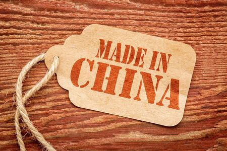 made in China  sign - red stencil text on a paper price tag against grunge wood