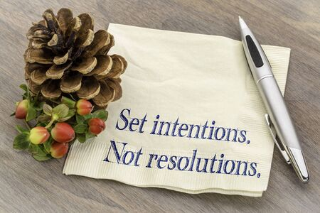 Set intentions. Not resolutions. New Year goals concept.  Handwriting on a napkin with a pine cone. Stock Photo