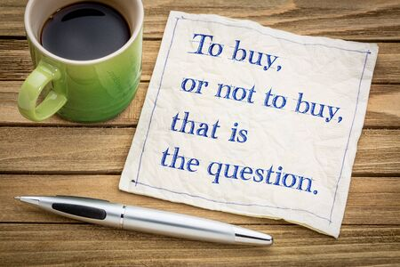 To buy, or not, that is the question. SHpping and decsion copncept. Handwriting on a napkin with a cup of coffee.
