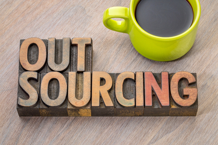 outsourcing word abstract in vintage letterpress wood type with a cup of coffee