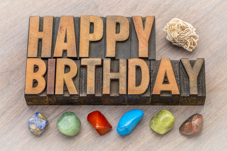 Happy Birthday greeting card in vintage letterpress wood type against grained wood with colorful polished stones and gypsum rosette