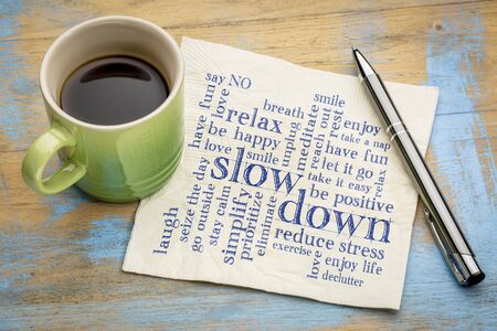 slow down and relax - reducing stress tips in a form of a word cloud on a napkin with a cup of coffee Stock Photo