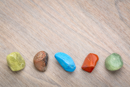 row of semiprecious colorful polished gemstones against grained wood with a copy space