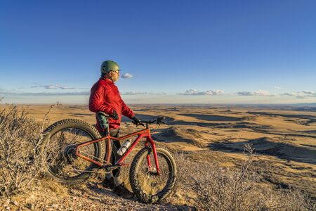 senior cyclist with a fat bike contemplating sunset over  Colorado prairie and foothills in Soapstone Prairie Natural Area, fall scenery