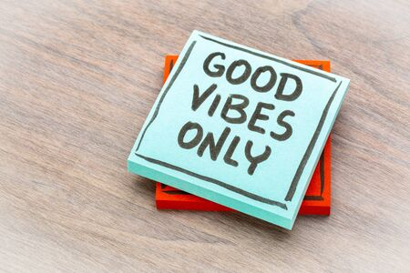 Good vibes only reminder - handwriting on a sticky note against grained wood 스톡 콘텐츠
