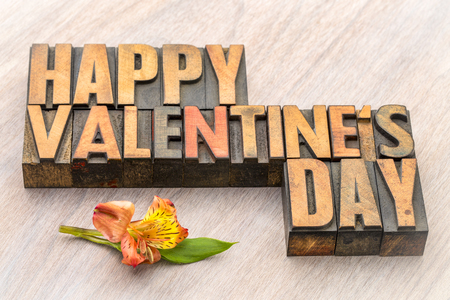Happy Valentines Day  in vintage letterpress wood type blocks with an orchid flower Stock Photo