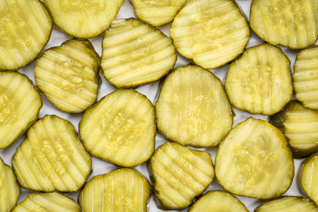 slices of cucumber pickles - background on a white plate