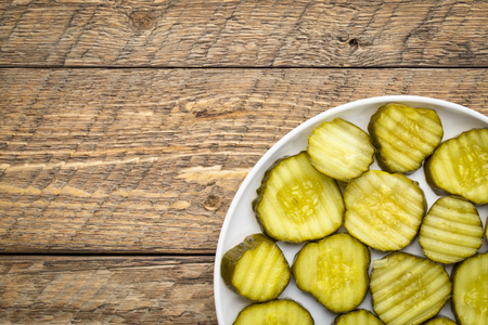 slices of cucumber pickles on a  white plate against rustic wood table Banco de Imagens