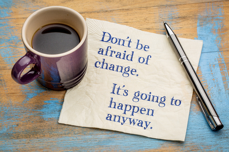 Dont be afraid of change. Its going to happen anyway. Handwriting on a napkin with a cup of espresso coffee