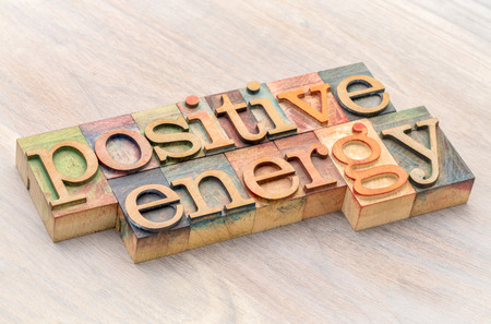 positive energy word abstract in letterpress wood type against grained wood