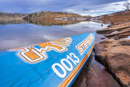 Fort Collins, CO, USA - January 6, 2018: : A bow of  All Star racing stand up paddleboard by Starboard with a race number on a rocky shore of Horsetooth Reservoir.